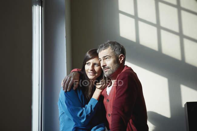 Пара сидять у вікні програми, посміхаючись на дому — стокове фото