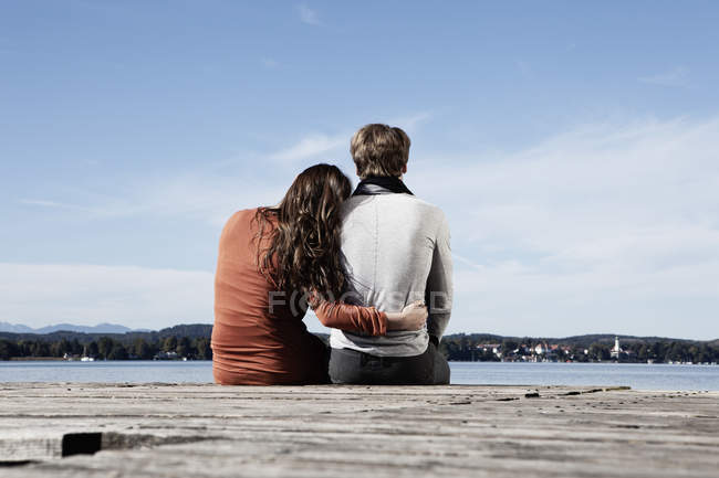 Couple sitting on jetty at lakeside — Stock Photo