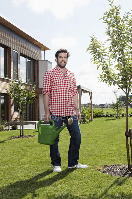 Mature man with watering can in garden — Stock Photo