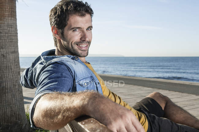Spain, Mid adult man sitting on bench, smiling, portrait — Stock Photo