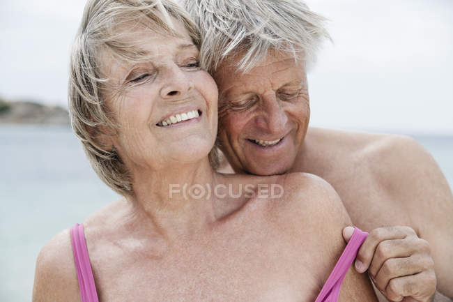 Casal sênior despir na praia — Fotografia de Stock