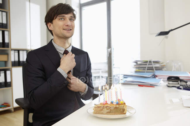 Mid adult man with birthday cake, smiling — Stock Photo