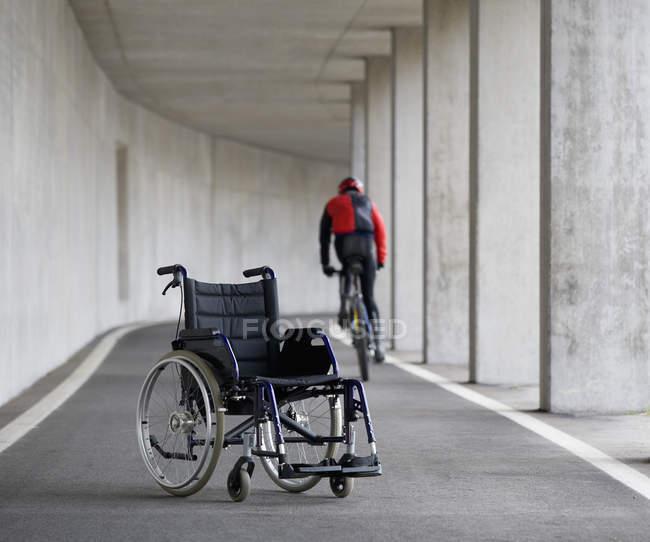 Jovem na montanha com cadeira de rodas em primeiro plano — Fotografia de Stock