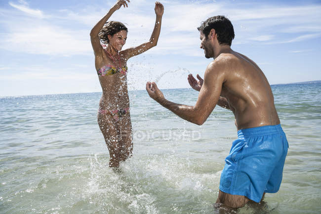 Mid adult couple playing in sea at beach — Stock Photo