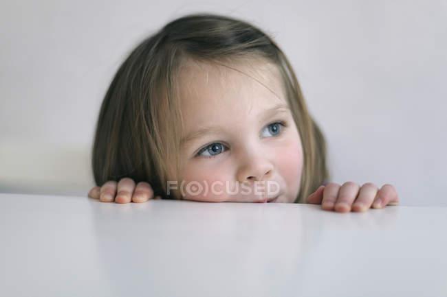 Портрет дівчині, що ховається за столом — стокове фото
