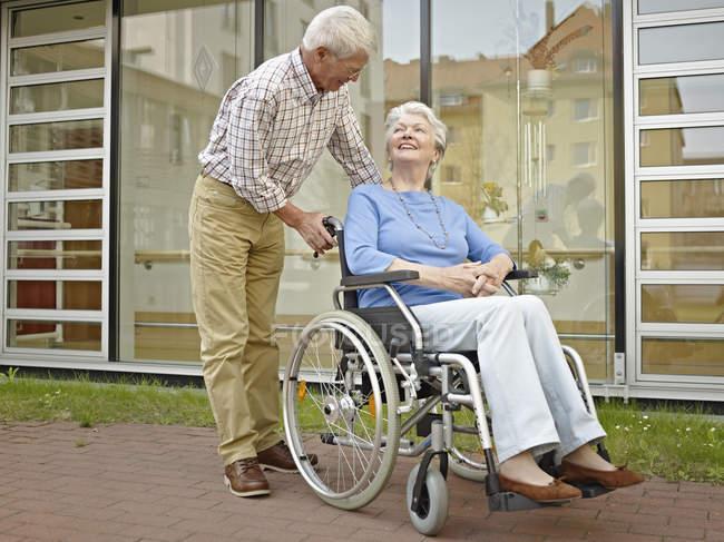 Senior homme poussant femme en fauteuil roulant — Photo de stock