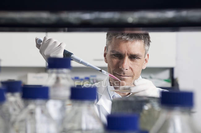 Scientist pouring liquid with pipette — Stock Photo