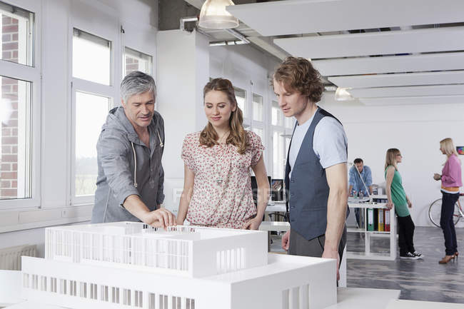 Man explaining architectural model to colleagues — Stock Photo