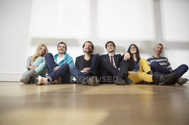 Men and women sitting on floor in modern office — Stock Photo
