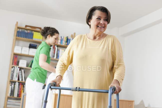 Старші жінки прогулянки з ходьба кадр іншу жінку, організацію ліжко медична — стокове фото