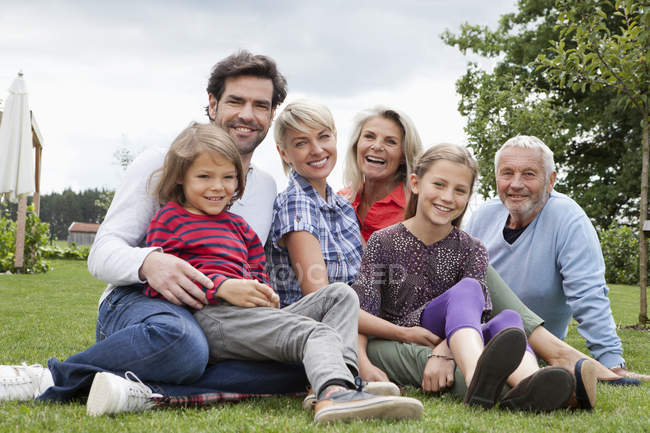 Сім'я, сидячи на траві, посміхаючись, портрет — стокове фото