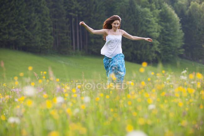 Молодая женщина бежит в поле цветов — стоковое фото