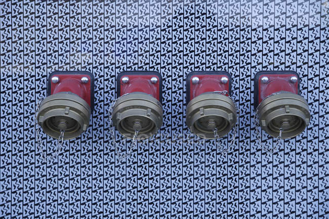 Row of water hydrants for fire on wall — Stock Photo
