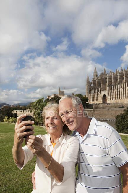 Испания, Майорка, Пальма, Старшая пара улыбается фотографируясь с собором Санта Мария, портрет — стоковое фото