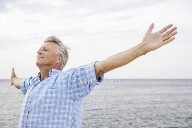 Senior man standing with arms outstretched on beach — Stock Photo
