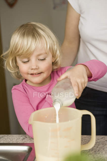 Girl pouring milk into measuring cup — Stock Photo