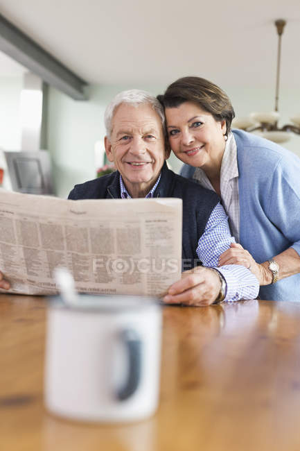 Senior man and woman with newspaper, smiling, portrait — Stock Photo