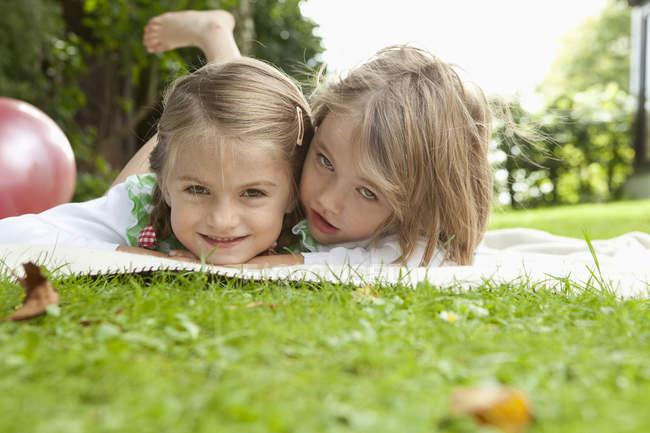 Smiling little girls lying on blanket in garden — Stock Photo