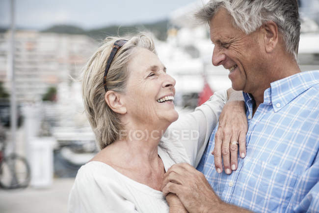 Senior couple at harbour looking at each other — Stock Photo
