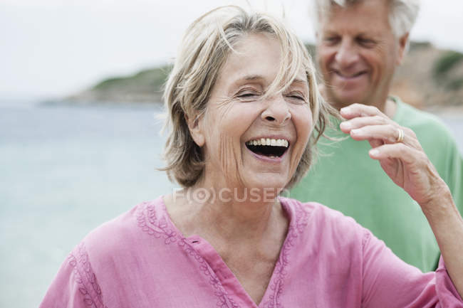 Happy Senior couple laughing at beach — Stock Photo