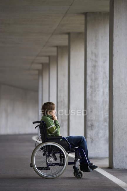 Молодой человек, сидя на инвалидной коляске в метро — стоковое фото