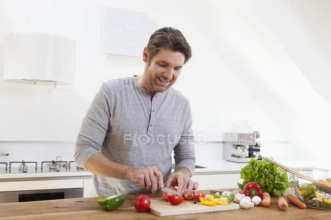 Homem cortando legumes na cozinha — Fotografia de Stock