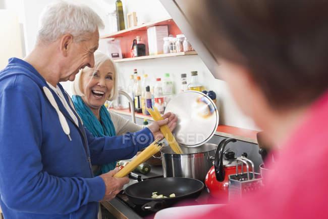 Мужчины и женщины готовят еду — стоковое фото