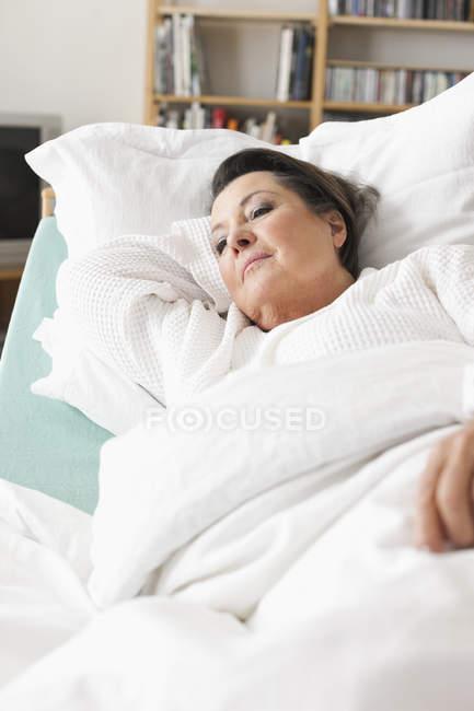 Senior mulher relaxante na cama médica — Fotografia de Stock