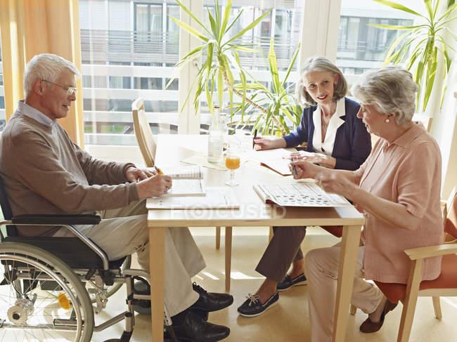 Mann im Rollstuhl mit Frauen im Pflegeheim — Stockfoto