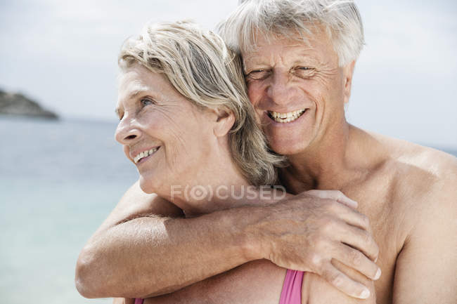 Senior couple embracing on beach — Stock Photo
