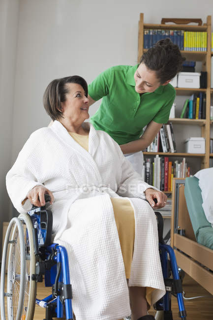 Senior woman sitting on wheelchair, mid adult woman standing beside — Stock Photo