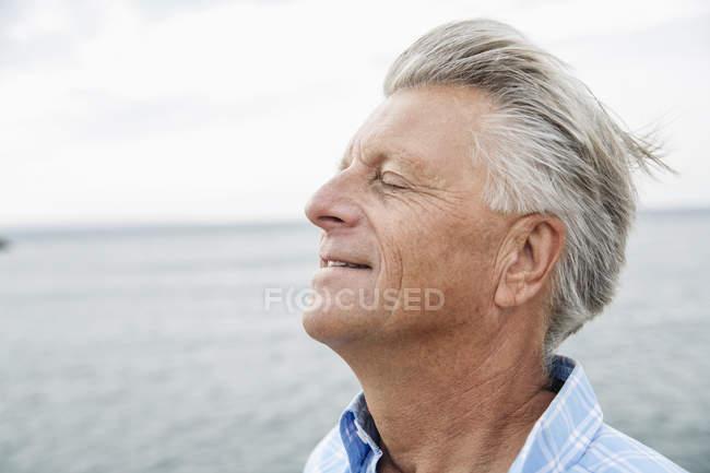 Senior man with closed eyes enjoying nature — Stock Photo