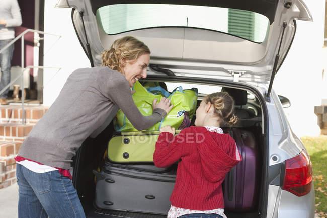 Мать и дочь грузят багаж в машину — стоковое фото