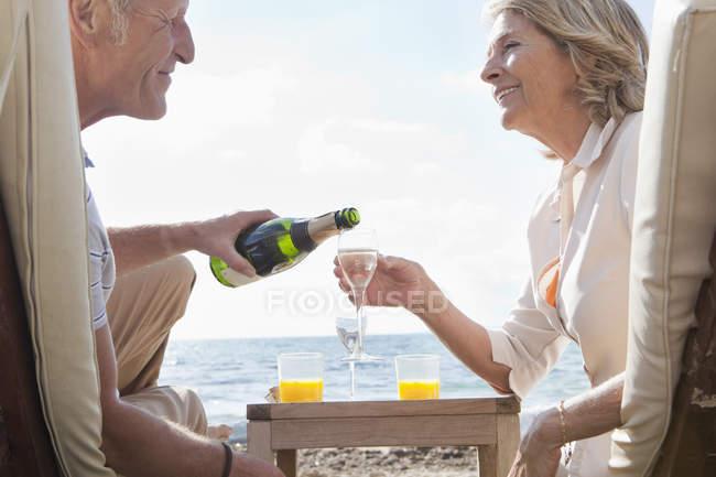 Старший пара ігристе вино пили на пляжі — стокове фото