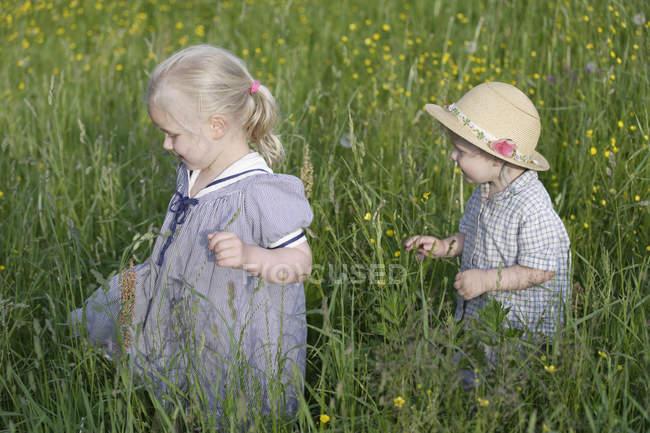 Germany, Bavaria, Girl and boy walking through meadow — Stock Photo