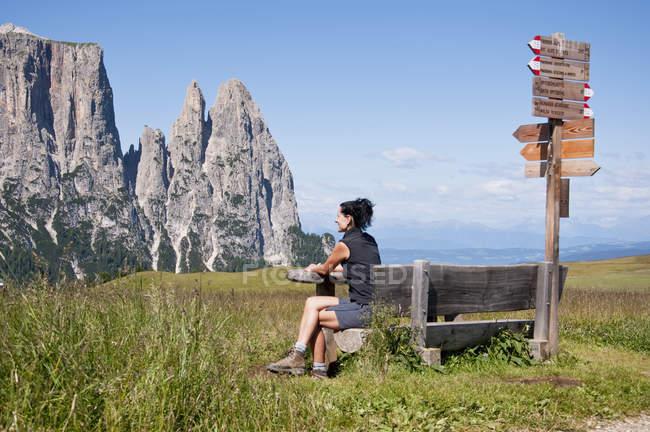 Italia, Donna adulta seduta sulla panchina e in cerca di Schlern in Alto Adige — Foto stock