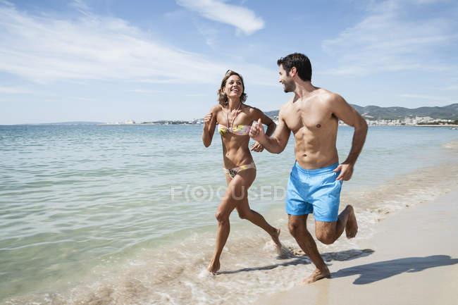 Средний взрослый пара работает на пляже в Купальники — стоковое фото
