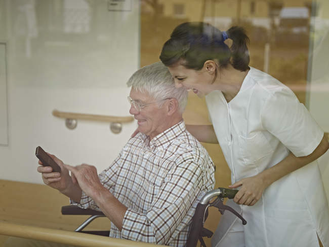 Senior man sitting in wheelchair with phone — Stock Photo