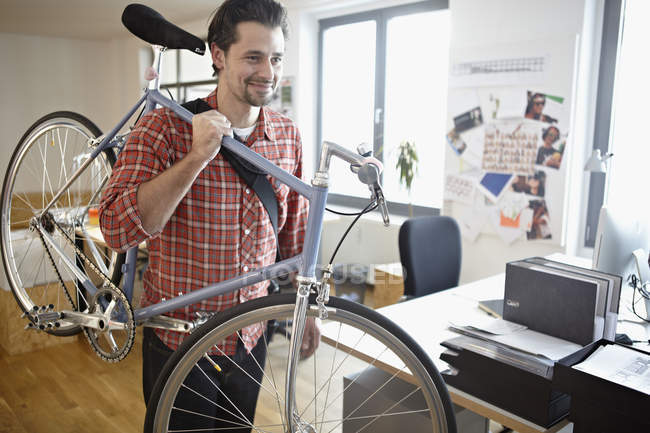 Mid adult man carrying bicycle, smiling — Stock Photo