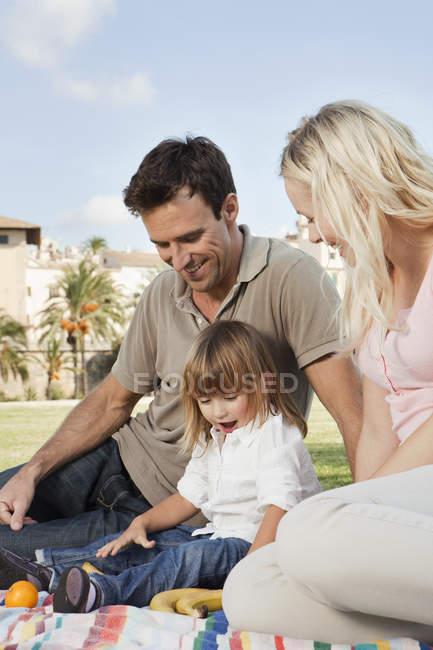 Улыбающаяся семья, сидящая на одеяле с фруктами — стоковое фото