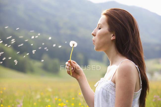 Giovane donna che soffia dente di leone nel campo dei fiori — Foto stock