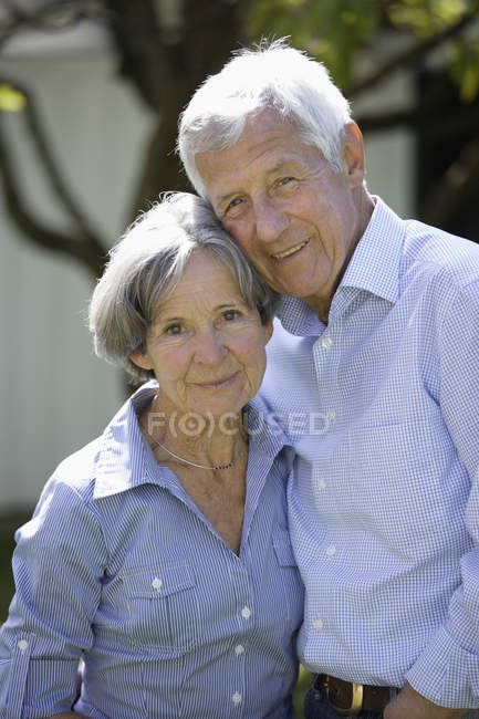 Senior couple smiling outdoors, portrait — Stock Photo