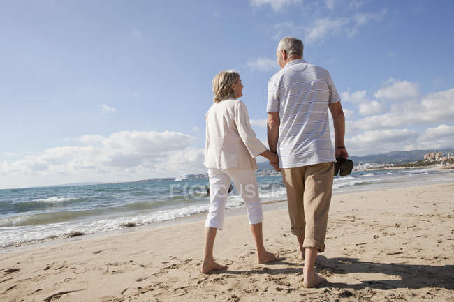 Senior couple walking along beach — Stock Photo