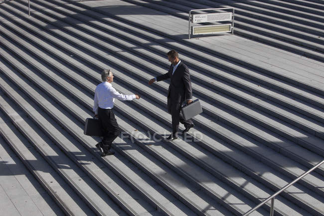 Engineers shaking hands on stairs — Stock Photo