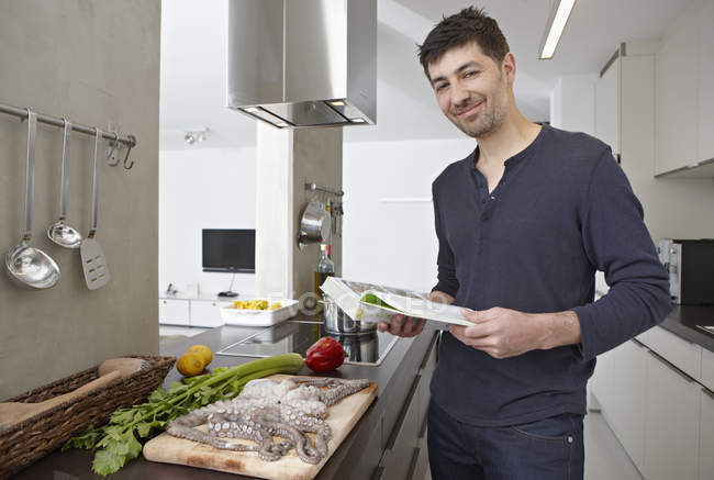 Mid adult man with cook book in kitchen, portrait — Stock Photo