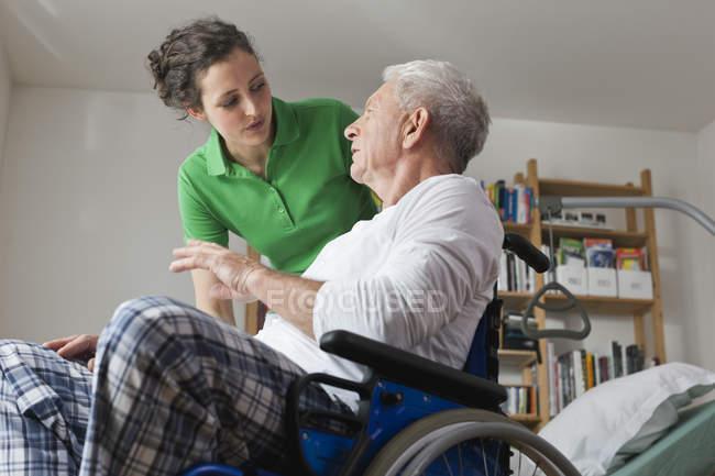 Чоловік на інвалідному візку, говорити з жінкою — стокове фото