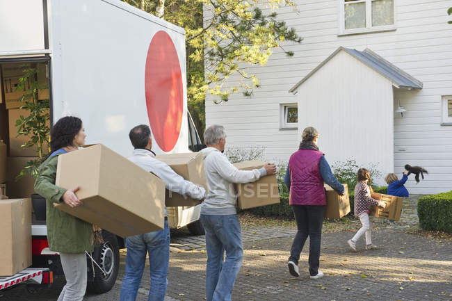 Family carrying cardboard box for moving house — Stock Photo