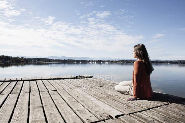 Молодая женщина сидит на пристани — стоковое фото