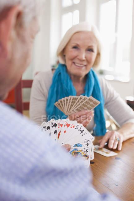 Старший мужчина и женщина играют в карты, улыбаясь — стоковое фото