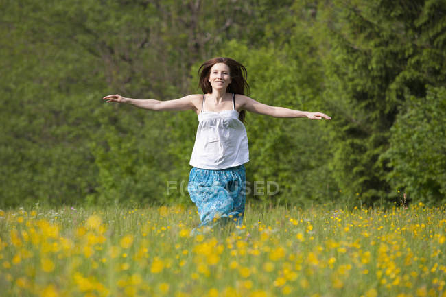 Young woman running in field of flowers — Stock Photo